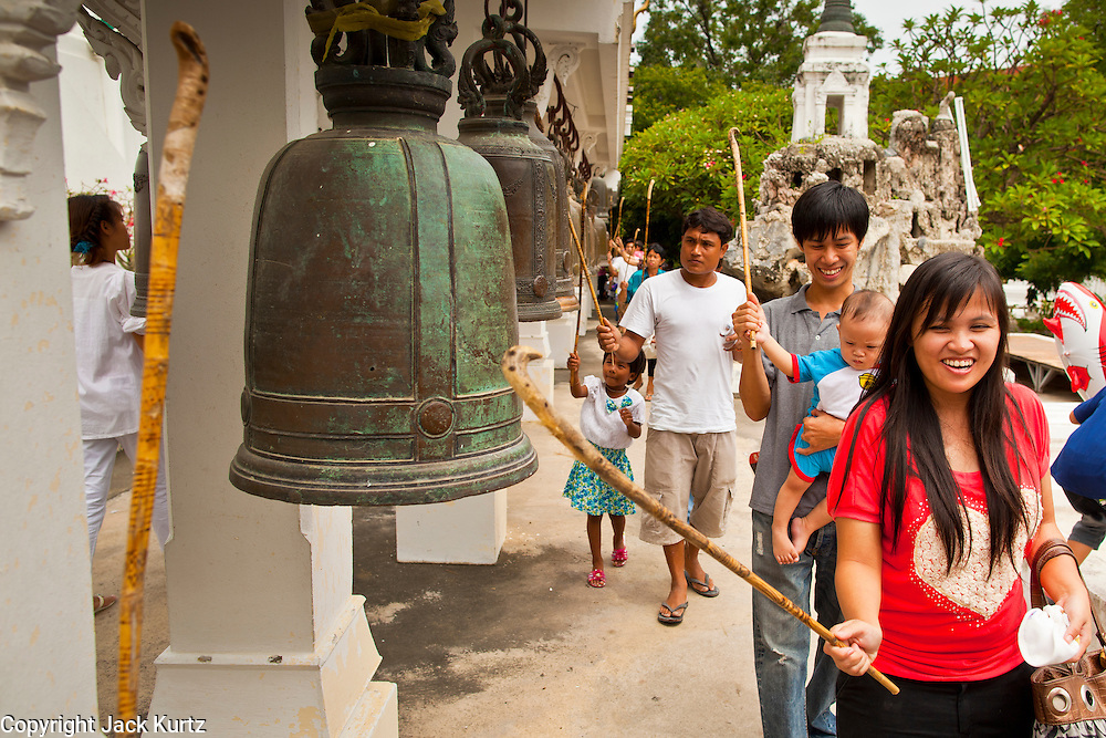 "15 JULY 2011 - PHRA PHUTTHABAT, SARABURI, THAILAND:  People ring holy prayer bells at Wat Phra Phutthabat in Phra Phutthabat, Saraburi, Thailand. The temple is famous for the way it marks the beginning of Vassa, the three-month annual retreat observed by Theravada monks and nuns. The temple is highly revered in Thailand because it houses a footstep of the Buddha. On the first day of Vassa (or Buddhist Lent) people come to the temple to ""make merit"" and present the monks there with dancing lady ginger flowers, which only bloom in the weeks leading up Vassa. They also present monks with candles and wash their feet. During Vassa, monks and nuns remain inside monasteries and temple grounds, devoting their time to intensive meditation and study. Laypeople support the monastic sangha by bringing food, candles and other offerings to temples. Laypeople also often observe Vassa by giving up something, such as smoking or eating meat. For this reason, westerners sometimes call Vassa the ""Buddhist Lent."" The tradition of Vassa began during the life of the Buddha. Most of the time, the first Buddhist monks who followed the Buddha did not stay in one place, but walked from village to village to teach. They begged for their food and often slept outdoors, sheltered only by trees. But during India's summer rainy season living as homeless ascetics became difficult. So, groups of monks would find a place to stay together until the rain stopped, forming a temporary community. Wealthy laypeople sometimes sheltered monks on their estates. Eventually a few of these patrons built permanent houses for monks, which amounted to an early form of monastery.    PHOTO BY JACK KURTZ"