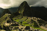 A momentary burst of sun through the clouds lights the ruins of the Inca city of Machu Picchu. Huayna Picchu towers in the background.