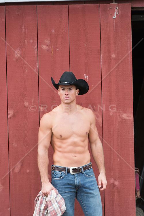 Shirtless muscular cowboy by a barn door