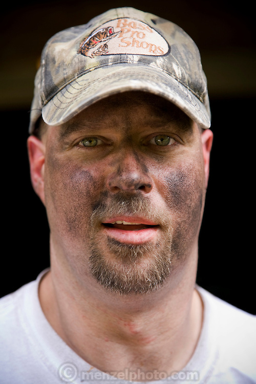 Todd Kincer, a coal miner, with his face blackened with coal dust after an industrious day at work in a coal mine located deep inside a mountain in the Appalachians near the town of Whitesburg, Kentucky. (Todd Kincer is featured in the book What I Eat: Around the World in 80 Diets.) After showering and scrubbing off the day's coal dust, Todd gets ready to dig in to one of his favorite meals: Hamburger Helper with double noodles. A college graduate drawn to the coal mine by the relatively high pay, Todd spends a 10-hour shift mining underground, driving a low-slung electric shuttle car that carries coal from the face of the coal seam, where it's being chewed up by a deafening, dusty mining machine, to a conveyer belt. The coal mine in which Kincer works is pitch-black, except for headlights and headlamps. During winter months, Todd never sees daylight during the workweek. MODEL RELEASED.