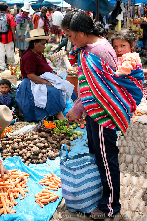 Americas, South America, Peru, Pisac. A young mother buying food with baby on her back at Pisac.