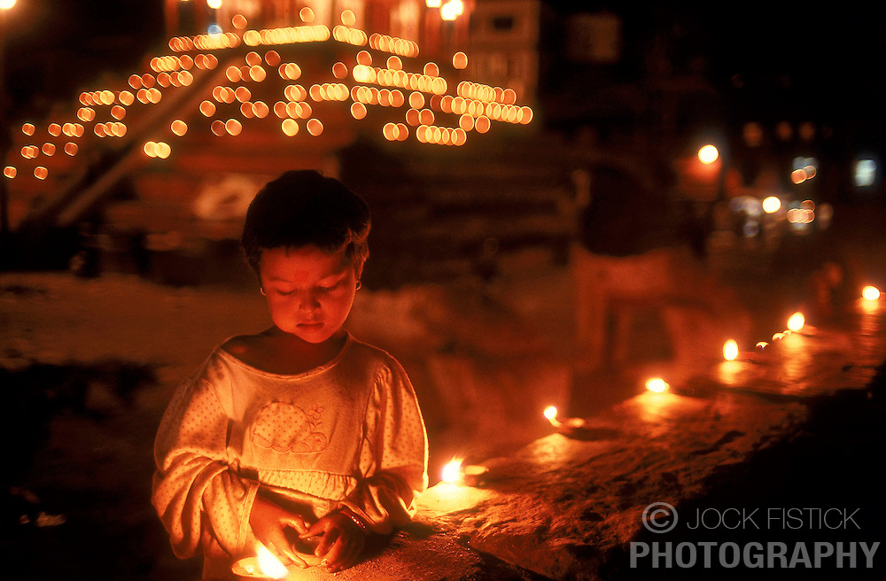 KATHMANDU, NEPAL - In Kathmandu's Dubar Square, a young girl lights mustard oil lamps on the eve of Tihar, the Festival of Lights, which is celebrated for five days in the fall. Tihar is a time when brothers and sisters pay respect to one another. The women serve an elaborate meal to the men, while the men return the gesture by giving a gift, usually money. On the fifth day, brothers and sisters pray to Yama, the god of death, that long life and prosperity be granted to their family. (Photo © Jock Fistick)