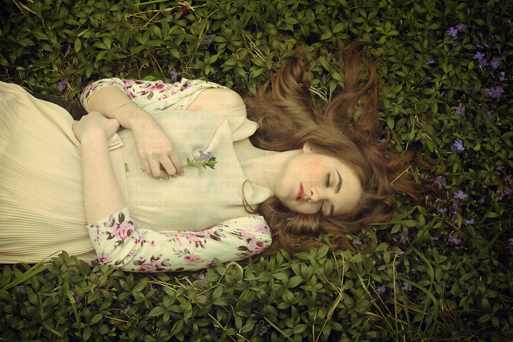 Female youth lying in flowers outdoors in spring | Trigger Image