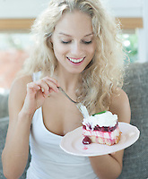 Beautiful woman having raspberry cake in house