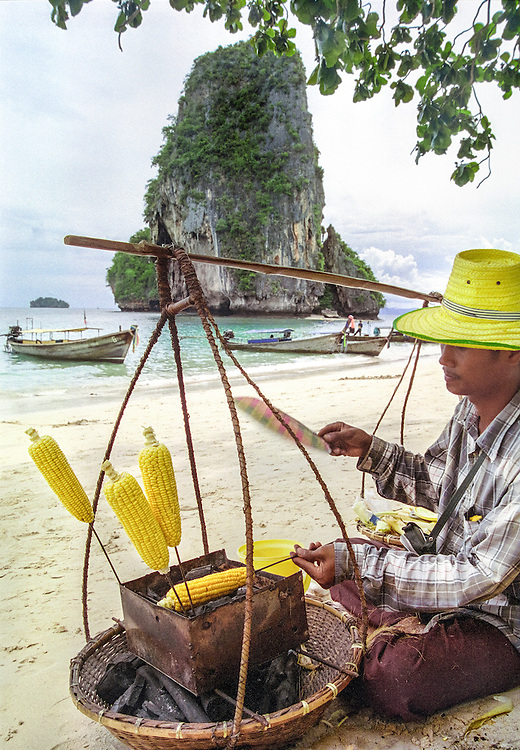 A man sells delicious grilled corn on the cob on Ao Phra Nang beach, on the Raileh peninsula, Thailand, 2003.