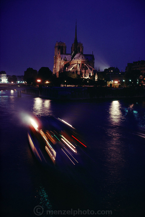 Notre Dame Cathedral at dusk with the lights of a passing Bateau Mouche on the Seine River, Paris, France.