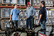01/14/2016 133619 -- Garland, TX -- © Copyright 2016 Mark C. Greenberg<br /> <br /> From left: President and COO Rick Sukkar and CEO Alex Keechleof talk with warehouse manager Kevin Sadler in the warehouse of Garland, Texas based Monster Moto