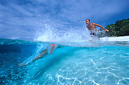 Man & woman racing into clear waters off a remote island in the Ha'apai group of islands. Tonga.To use this image please contact Getty Images. Getty #20011936-001