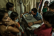 "SAN CASIMIRO, VENEZUELA - AUGUST 21, 2017: Carlos Aquino, 37, weeps uncontrollably surrounded by his nieces and nephews, over the body of his 17-month old son, Kenyerber Aquino Merchan - who died of heart failure caused by severe malnutrition. Though tears, Carlos cried, ""My God, how can this be? You left me alone…your papá will never see you again!"" He rested his cheek near the glass above Kenyerber's face, and hugged the tiny coffin - speaking softly as if to comfort his son through the transition between life and death - telling him of family members already in heaven, who would take care of him. ""Your grandfather is going to love you,"" he said. ""Let me know when you see him."" Kenyerber weighed only 8.8 lbs when he died - less than half the recommended body weight for a 17-month old. He was born healthy, weighing 6 lbs, 7 ounces - but his mother, María Carolina Merchan, 29, got infected by the Zika virus when he was three months old. She had to be hospitalized when she fell ill to the Zika related Guillain-Barré Syndrome - that made it impossible for her to continue to breast feed Kenyerber.  The economic crisis in Venezuela has led to widespread shortages of infant formula, and when the family could not access it to feed Kenyerber, they had to improvise - feeding him what they could find: cream of rice or cornstarch mixed with whole milk, neither of which could provide him the nutrients he needed. He was first admitted into the hospital for malnutrition when he was 9 months old - and was in and out of the hospital for treatment for malnutrition until he died on August 19, 2017 at Domingo Luciani Hospital in the Sucre municipality of Venezuela.  PHOTO: Meridith Kohut for The New York Times"