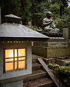 A lantern and a statue of a Buddhist priest.
