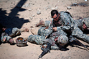 A medic responds to mayhem after a simulated explosion seemingly destroys an Army Humvee inside the fabricated Iraqi village of Medina Wasl, built by set coordinators from Paramount Pictures  at Fort Irwin, California, in the Mojave Desert, California. (From the book What I Eat: Around the World in 80 Diets.) Hundreds of military and civilian actors and scores of directors participate in elaborate training exercises for soldiers deploying to Iraq. Some actors are actually amputees, adding to the realism of the scene, which is embellished with fake blood and dismembered limbs.