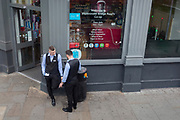 Work mates share a cigarette break outside a Co-Op in Southwark, on 26th March 2019, in London, England