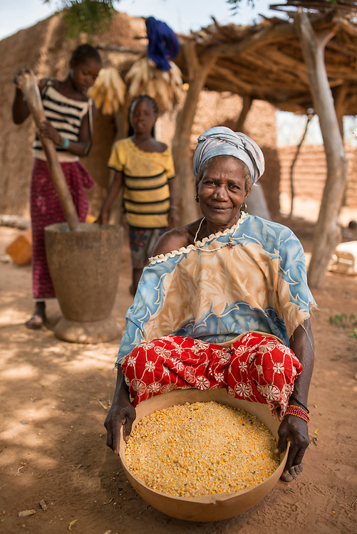 Family gathered after grinding corn (maize) into meal for cooking in the village of Bagui Traue, near Kolokani, Mali.