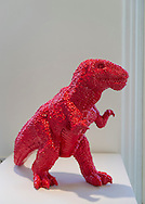 """Roslyn, New York, USA. January 2, 2015. Dinosaur (2006) in red polyresin, by Chinese artist Sui Jianguo (b. 1956) is displayed at the Nassau County Museum of Art China Now and Then Exhibit. """"MADE IN CHINA"""" is written in big block letters down his chest."""