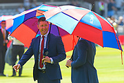 TV presenters shade themselves with umbrellas to protect themselves from the scorching hot sunshine during  the World Cup 2019 match between New Zealand and Australia at Lord's Cricket Ground, St John's Wood, United Kingdom on 29 June 2019.