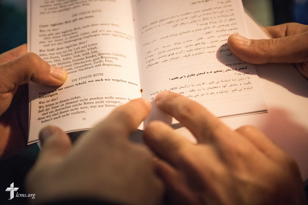 Refugees read through a translated Luther's Small Catechism during Bible study on Friday, Nov. 13, 2015, near the Evangelisch-Lutherische St. Trinitatisgemeinde, a SELK Lutheran church in Leipzig, Germany. LCMS Communications/Erik M. Lunsford