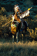 THIS PHOTO IS AVAILABLE FOR WEB DOWNLOAD ONLY. PLEASE CONTACT US FOR A LARGER PHOTO. An Indian Chief sits with authority on his horse in the countryside at sunset.  MR