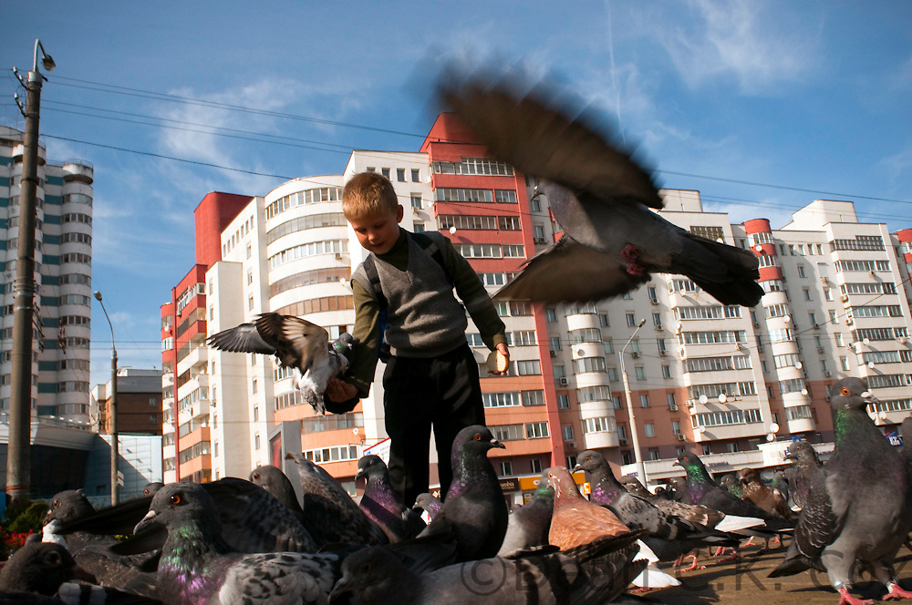 A boy feeds pigeons near the main indoor Komarovski covered market in Minsk on Sept. 28, 2009. Minsk was almost completely flattened during World War II and now boasts architecture dating primarily from the Soviet era.