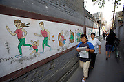 Traditional Sanjing Hutong (old quarter). Educational wall paintings. One-child-family propaganda.