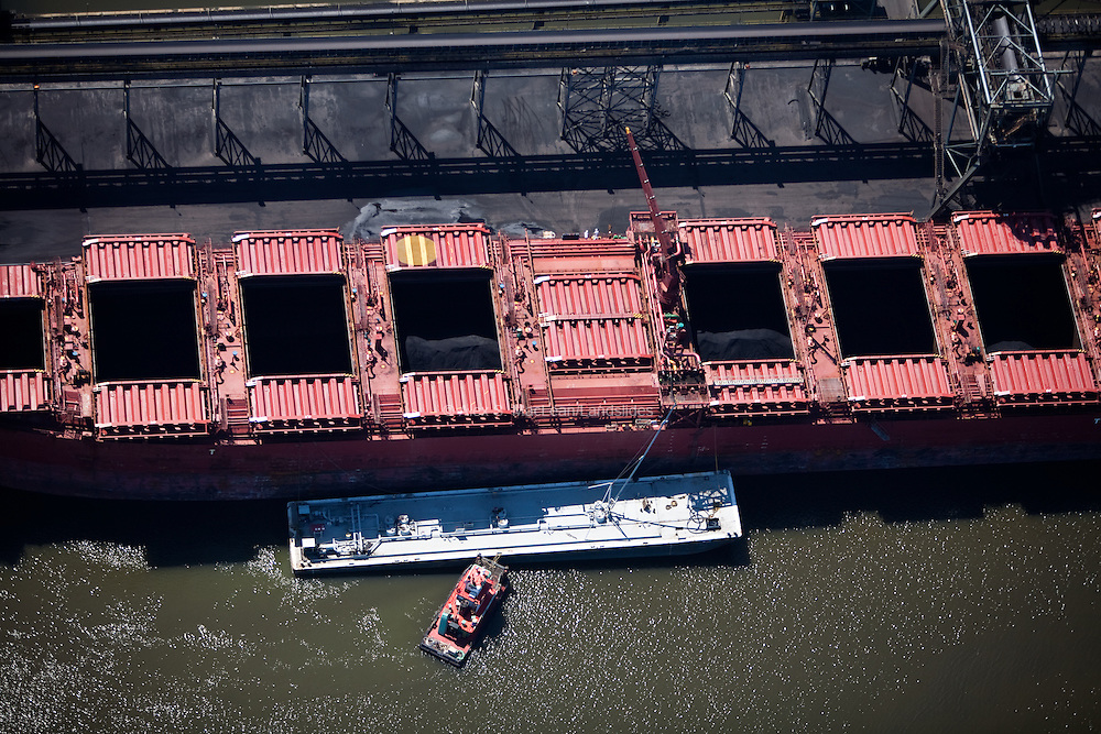 A tug boat and barge work together to load a coal freighter.