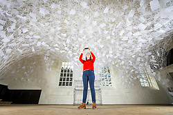 © Licensed to London News Pictures. 28/03/2018. Wakefield UK. Lydia Turnbull looks at the new exhibition by Chiharu Shiota called Beyond Time. Yorkshire Sculpture Park welcomes a site-specific installation by artist Chiharu Shiota, The sculpture is on show in the 18th century chapel & is made using over 2000 balls of wool. Photo credit: Andrew McCaren/LNP