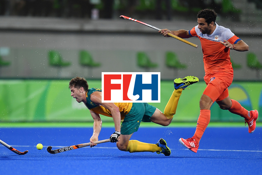 Australia's Eddie Ockenden (L) falls on the pitch as he vies with Netherland's Valentin Verga during the men's quarterfinal field hockey Netherlands vs Australia match of the Rio 2016 Olympics Games at the Olympic Hockey Centre in Rio de Janeiro on August 14, 2016. / AFP / MANAN VATSYAYANA        (Photo credit should read MANAN VATSYAYANA/AFP/Getty Images)
