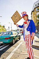 "Uncle Sam standing on the side of the road at an intersection holdinga a sign saying ""my job was shipped overseas""...Model Release: 20080813_MR_A"