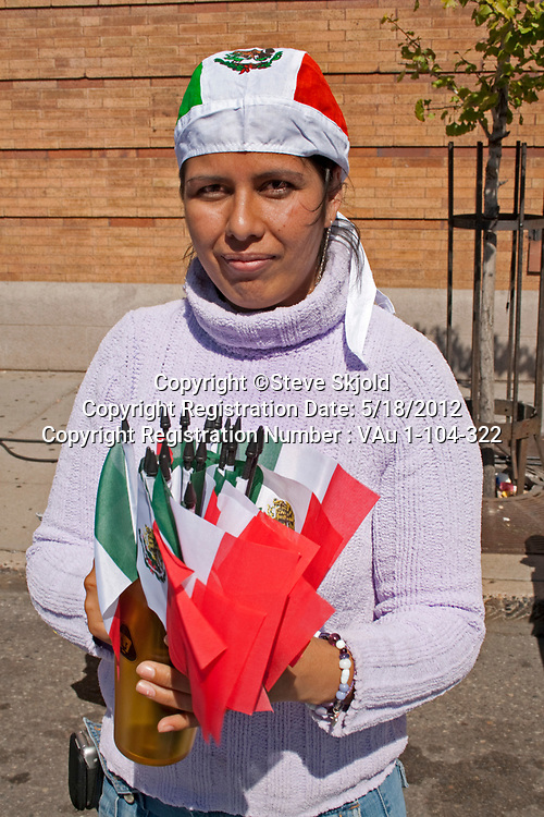 Latino woman selling small Mexican flags by the handful. Mexican Independence Day Minneapolis Minnesota MN USA