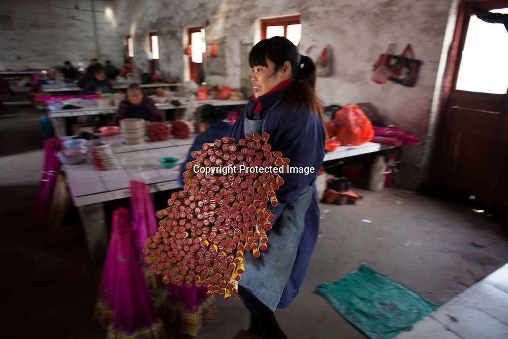 Hunan, Liuyang, Dec. 19..2013 : LUO YUNLIAN, 34, a worker, assembles  fireckrackers for the Western market in a factory .