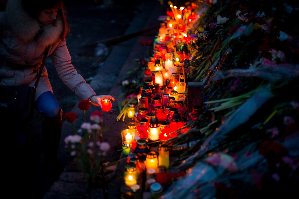 "A young woman lights up a candle on an improvised memorial to the ""heroes of Maïdan"", on the Independance Square, in Kiev."