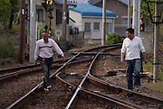Two men walking along railway tracks of the Yoro Line near Tado Station, Japan.