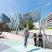 Foto :David Rozing. Wateropvang, waterplein Benthemplein: het eerste grootschalige waterplein. Rotterdam heeft het eerste grote waterplein van de wereld. Scholieren van het Zadkine chillen op het plein, spelen basketball op het basketball veldje en zitten op de trappen van de grote waterput. Het waterplein wordt door de curves welvingen ook gebruikt om te skaten, door skaters. Een mooi plein midden in de stad, dat helpt om droge voeten te houden.<br /> Bij droog weer zijn er mooie plekken om te basketballen en te skaten, bij zware regenval kunnen de bassins het regenwater van het plein en de daken opvangen. Bij elkaar ongeveer 1,7 miljoen liter water. Dat water hoeft daardoor niet meer naar het riool, dat dus minder snel zal overstromen. En zo helpt het plein om droge voeten te houden terwijl regenbuien steeds heftiger worden. Een aantal studenten van scholen uit de buurt hebben bij de gemeente Rotterdam gevraagd of het mogelijk was het plein aan te passen. Dit paste uitstekend bij de wens van de gemeente en het Hoogheemraadschap van Schieland en de Krimpenerwaard om in de buurt een waterplein aan te leggen. plein in de weekenden gebruikt door skaters en bootcampers. Rotterdamse innovatie. Zoals veel steden, is Rotterdam dicht bebouwd. De stad heeft veel gebouwen en nog veel meer bestrating. Tegelijk worden regenbuien steeds heftiger, waardoor de kans op wateroverlast in de stad toeneemt. In Rotterdam zijn weinig mogelijkheden om extra ruimte te maken voor water, zoals singels, met name in de binnenstad. Zo ontstond in 2005 het idee van het waterplein: een plein dat bij droog weer een aantrekkelijke, leuke omgeving biedt, en dat er bij heftige regenbuien voor zorgt dat er minder water naar het riool en de singels stroomt. Op het Benthemplein worden alle principes van het waterplein toegepast De riolering is aangepast om de werking te optimaliseren. De regenpijpen van de gebouwen rond het plein komen niet meer uit op de riolering; het water van de daken stroomt nu zi
