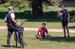 © Licensed to London News Pictures. 30/05/2020. London, UK. A Police officer speaks to a man with a dog in Richmond Park in South West London during lockdown as weather experts predict another warm weekend with highs of 28c. On Monday, up to six people will be allowed to meet up in parks and private gardens. Photo credit: Alex Lentati/LNP