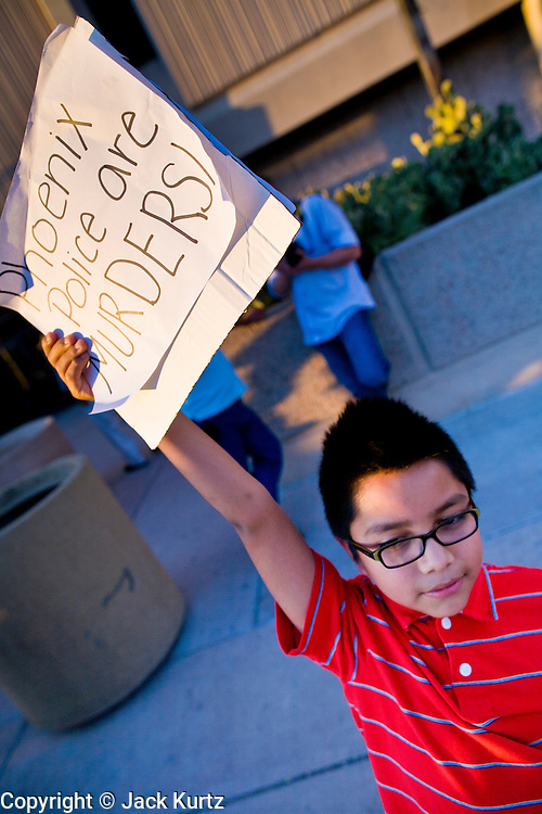 11 OCTOBER 2010 - PHOENIX, AZ:  A child pickets Phoenix police headquarters Monday night. About 300 people gathered at the Phoenix Police Department headquarters building Monday night to protest the shooting of Daniel Rodriguez and his dog. The officers responded to a 911 call made by Rodriguez' mother. A scuffle ensued when they arrived and Phoenix police officer Richard Chrisman shot Rodriguez, who was unarmed, and his dog. Chrisman then allegedly filed a false report about the event. He has been arrested on felony assault charges. The event has angered some in the Latino community and they have held a series of protests at the police headquarters. They want Chrisman charged with murder.    Photo by Jack Kurtz
