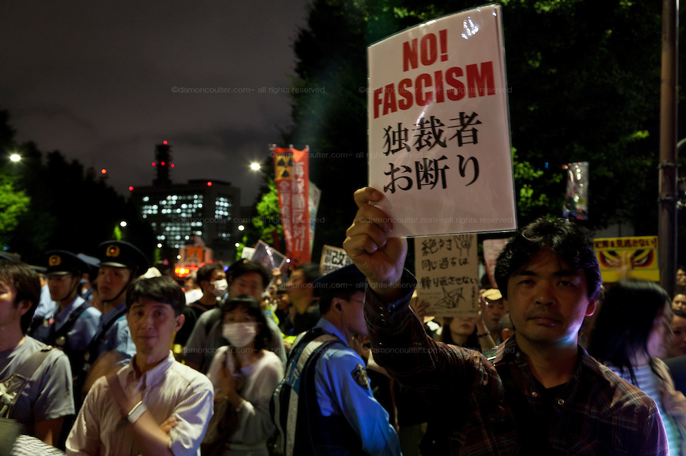 """A Japanese man holds a """"No Fascism!"""" sign at a protest against the revision of article 9 of the Japanese Constitution outside the Prime-Minister's house in Kasumigasaki, Tokyo, Japan. Monday June 30th 2014. Over 10,000 people showed their support for Japan's unique peace constitution and called on the government to halt its reinterpretation of Article 9 allowing Collect Self Defence which is expected to become law on July 1st"""