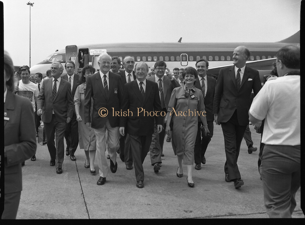 Irish Soccer Team Welcomed Home.   (R81)..1988..19.06.1988..06.19.1988..19th June 1988..After their great success in Germany in Euro 88, the Irish soccer team had a triumphant homecoming. An Taoiseach, Charles Haughey TD and his government were to the forefront of the welcome. Thousands of fans thronged the airport and all the approach roads in the hope of seeing the team. The full squad is as follows..1.GK.Packie Bonner. Celtic.2.DF.Chris Morris. Celtic.3.DF.Chris Hughton  Tottenham Hotspur.4.DF.Mick McCarthy. Celtic.5.DF.Kevin Moran. Manchester United.6.MF.Ronnie Whelan. Liverpool.7.MF.Paul McGrath. Manchester United.8.MF.Ray Houghton. Liverpool.9.FW.John Aldridge. Liverpool.10.FW.Frank Stapleton Derby County.11.MF.Tony Galvin. Sheffield Wednesday.12.FW.Tony Cascarino. Millwall.13.MF.Liam O'Brien. Manchester United.14.FW.David Kelly. Walsall.15.MF.Kevin Sheedy. Everton.16.GK.Gerry Peyton. Bournemouth.17.FW.John Byrne. Le Havre.18.FW.John Sheridan. Leeds United.19.DF.John Anderson. Newcastle United.20.FW.Niall Quinn. Arsenal..Image shows the  An Taoiseach,Charles Haughey TD, and members of government as they stroll across the tarmac at Dublin Airport.