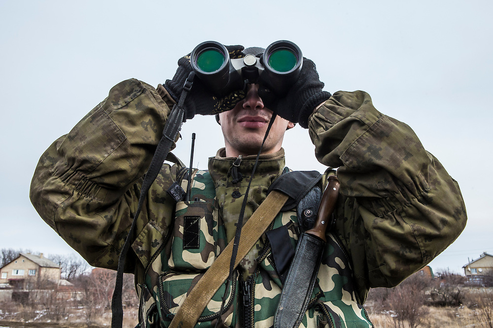 GORLOVKA, UKRAINE - JANUARY 31, 2015: A rebel fighter scans the horizon to monitor Ukrainian forces stationed a few kilometers away at a front-line position in Gorlovka, Ukraine. Fighting in Ukraine has intensified over the last week, with rebels declaring the end of a September ceasefire. CREDIT: Brendan Hoffman for The New York Times
