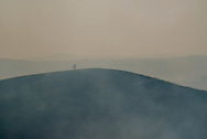A volunteer for the Konza Prairie Biological Station walks along a charred hill of the Konza Prairie off K-177 as smoke fills the valley South of Manhattan, Kansas on March 9, 2016. Every year the Flint Hills are set ablaze to help in an essential part of the delicate ecosystem.
