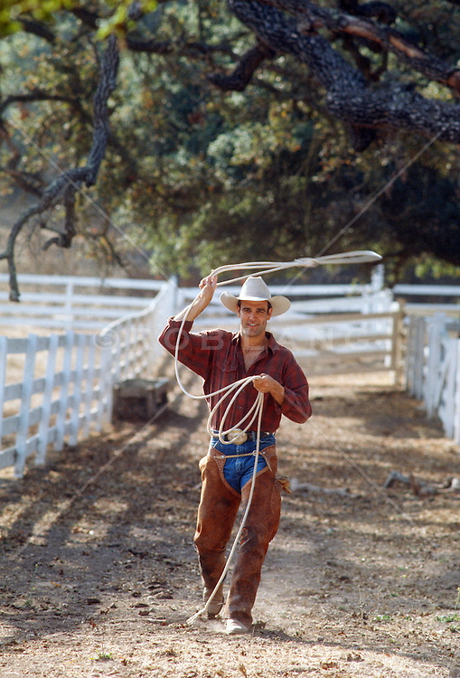 cowboy in chaps walking on a ranch while swinging a lasso
