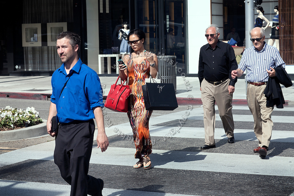 A woman (centre) is walking with boutique shopping bags while checking her phone along Rodeo Drive, the renowned shopping avenue running across Beverly Hills, Los Angeles, California, USA.