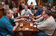 Five men play cards in a pub in the North of England while having a dink of beer.