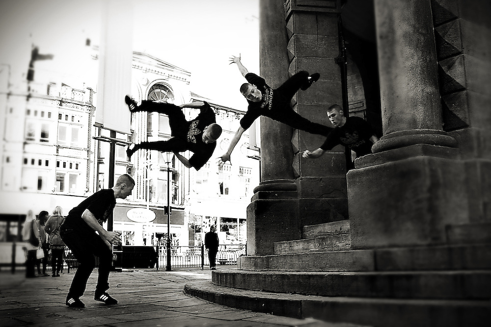 Black and white multiple / series shot of a free runner performing a side summie / flip down the steps of the Corn Exchange in Leeds, UK.