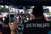 Onlookers watch a cultural performance during the VIII Festival for sovereignty and the People's right to self-determination in San Isidro's central park. Pacific Rim's controversial El Dorado gold mine has been the focus of numerous social conflicts at local and national level. Three anti-mining local leaders were murdered in 2009. While a year before, former president Antonio Saca refused to authorize the company's mining permit. This action prompted Pacific Rim to invoked a provision of the Central American Free Trade Agreement (CAFTA) to place the matter in the hands of an international arbitration court. Oceana Gold, who took over Pacific Rim on October 2013 for US $10.2 million , now seeks US $300 million for damages agains the State of El Salvador. San Isidro, Cabañas, El Salvador. September 15, 2014.