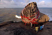 """THAILAND; Songkhla.Kao Seng fishing village (""""900,000 baht""""). Pilgrims wai the sacred stone which gives the fishing village of Kao Seng its name. Treasure said to be worth 900,000 baht is believed to lie beneath the boulder. It is supposed to have come from foreign merchants who kept it there for safe storage."""
