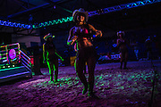 Cowgirls entertain the public in before the entrance of country singer and bull riding announcer Cuiabanno Lima at a rodeo ring prepared for his appearance  on a livestock compound  in Goiania, Brazil, Friday, Dec. 16, 2016. Considered one of the economic pillars of Brazil, hoarding increasingly huge swaths of land and spreading the same amounts of environmental degradation and land conflicts, the powerful agribusiness finds its heart, soul and voice in the city of Goiânia. Home of a million and a half souls it sits on the immense central plains of Brazil and nurtures a rodeo culture and cowboy lifestyle challenging its own urbanization, highlighting the archaic and rural character of Brazilian mindset and its society. Using cheap videoclips and broadcasting his tunes during rodeos he is invited, Lima showcases the maximum exponent of this  mentality. (Dado Galdieri for the New York Times)