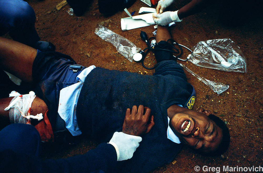 Dube, Soweto, 1994, South Africa: Army medics treat a manwho had been wounded in a train subway in Soweto. 1994.
