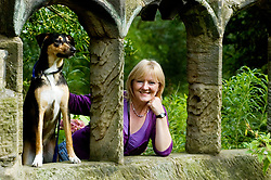 Young playful Black and Tan juvenile mongrel dog poses erect and alert looking through a ruined stone window beside his owner in Canon Hall Country Park <br />