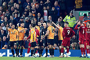 Wolverhampton Wanderers players surround Referee Anthony Taylor as they think there was a clear hand ball during the Premier League match between Liverpool and Wolverhampton Wanderers at Anfield, Liverpool, England on 29 December 2019.