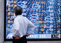 Man looking at stock prices on large video screen on a street in central Tokyo Japan