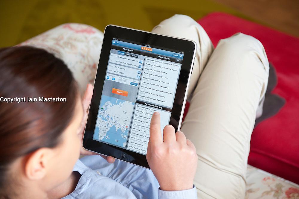 Woman using iPad tablet computer to plan travel using Kayak travel service application online
